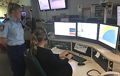 Senior Police Officer Overlooking Officer Working on Specialised Computer Console